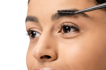 close-up view of beautiful african american woman combing eyebrow with brush and looking away isolated on white