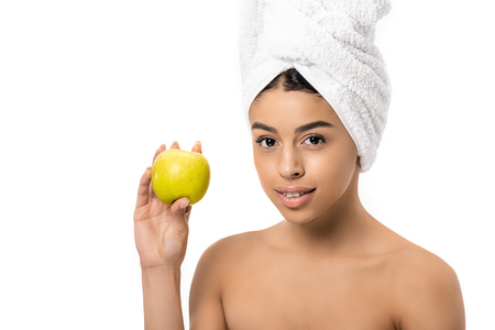 beautiful young african american woman with towel on head holding fresh apple and smiling at camera isolated on white