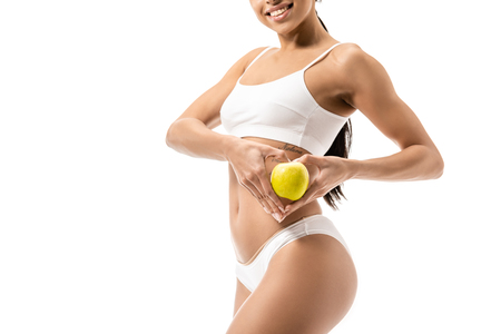 cropped shot of smiling young african american woman in underwear holding green apple isolated on white