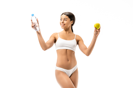 beautiful happy young african american woman in underwear holding bottle of water and green apple isolated on white