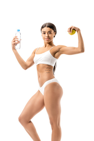 sporty african american girl in underwear holding bottle of water with green apple and showing muscles isolated on white Stockfoto