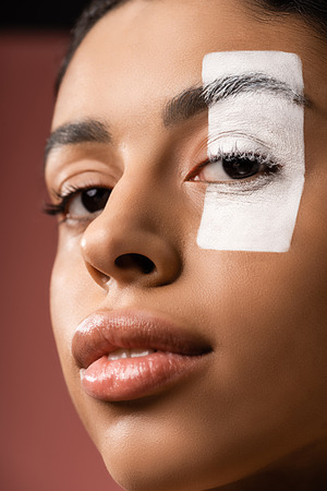 close-up view of attractive african american girl with white paint stroke on eye looking at camera isolated on brown Foto de archivo - 118638335