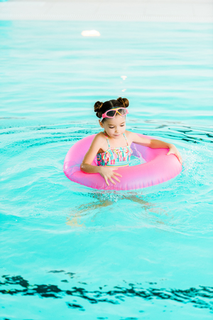 happy kid swimming with inflatable ring in swimming pool