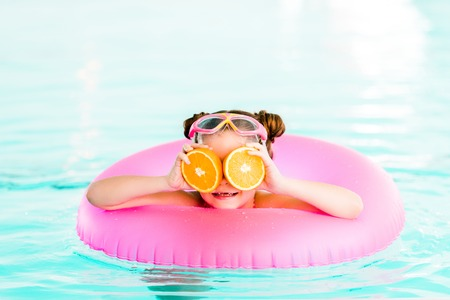 happy child holding half oranges near eyes while  swimming with inflatable ring in swimming pool Standard-Bild
