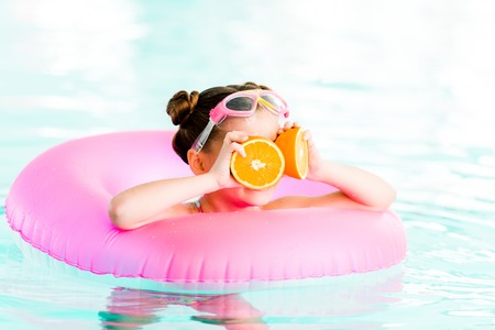 kid holding half oranges near eyes while  swimming with inflatable ring in swimming pool