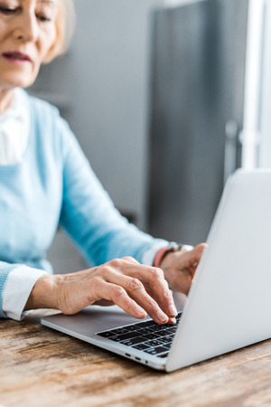 partial view of senior woman typing on laptop at home