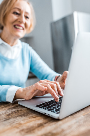selective focus of smiling senior woman typing on laptop at home Фото со стока