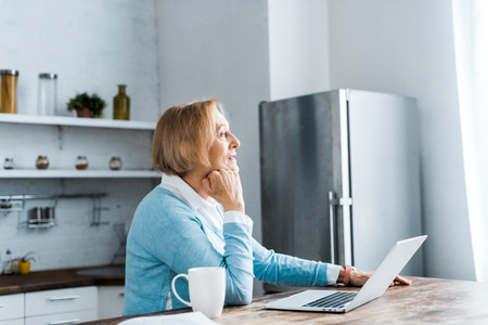 pensive senior woman sitting at table with cup of coffee and laptop in kitchen Stok Fotoğraf