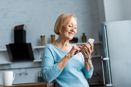 smiling senior woman using smartphone in kitchen