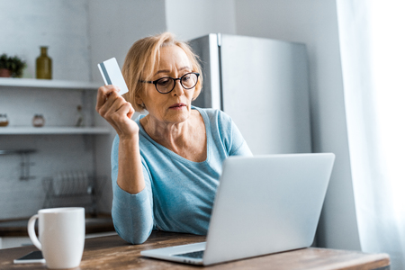 senior woman in glasses holding credit card and using laptop while doing online shopping at home 免版税图像
