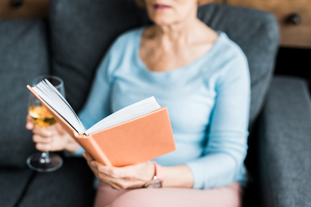 cropped view of senior woman sitting on couch, holding wine glass and reading book at home Zdjęcie Seryjne