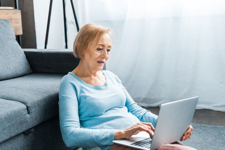 senior woman sitting and typing on laptop at home