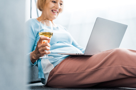 senior woman holding wine glass while having video call on laptop at home