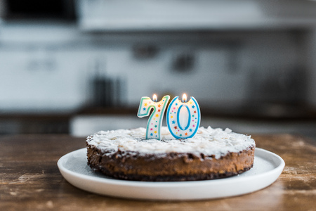 selective focus of delicious birthday cake with burning candles and 70 sign on top Banco de Imagens