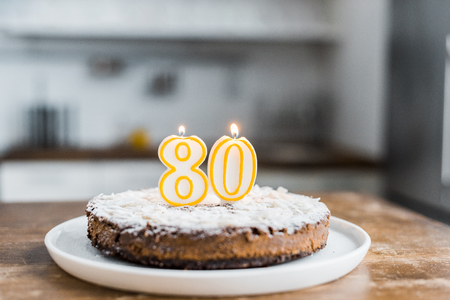 selective focus of delicious birthday cake with burning candles and 80 sign on top