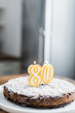 selective focus of delicious birthday cake with burning candles, copy space and 80 sign on top