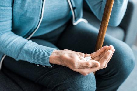Vista recortada de la mujer mayor enferma con bastón sosteniendo la medicina en la mano