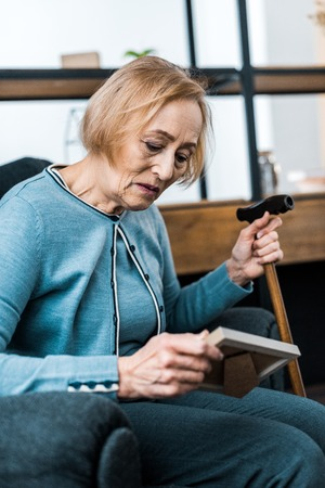 sad senior woman sitting with walking stick and looking at picture frame