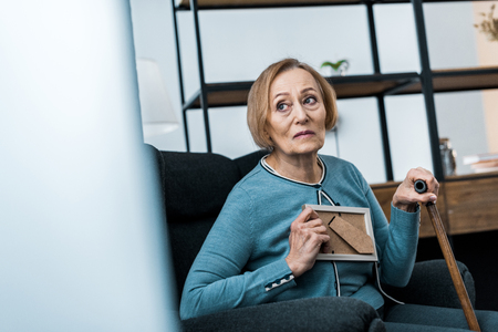 upset senior woman sitting with walking stick and holding picture frame at home