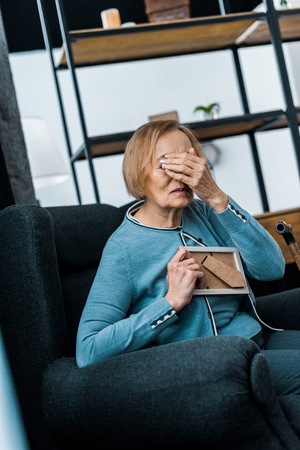 grieving senior woman sitting in armchair, covering face with hand and crying while holding picture frame Stock Photo