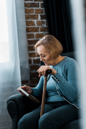 upset senior woman sitting with walking stick and looking at picture frame