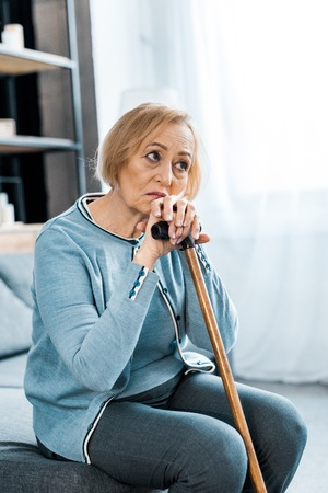 sad senior woman sitting on couch and holding walking stick at home with copy space
