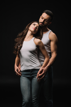 man hugging attractive woman in white singlet isolated on black
