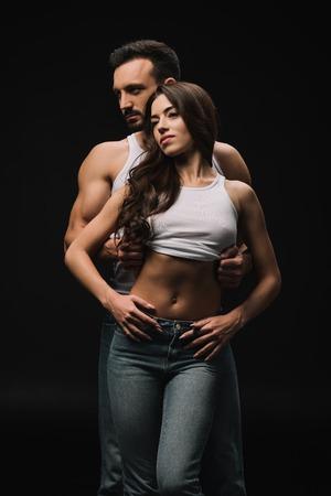 Gut aussehender Mann, der Frau im weißen Unterhemd auszieht, isoliert auf schwarz Standard-Bild