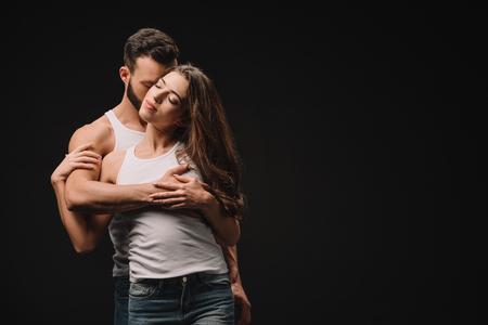 bel homme étreignant et embrassant une jeune femme isolée sur fond noir Banque d'images