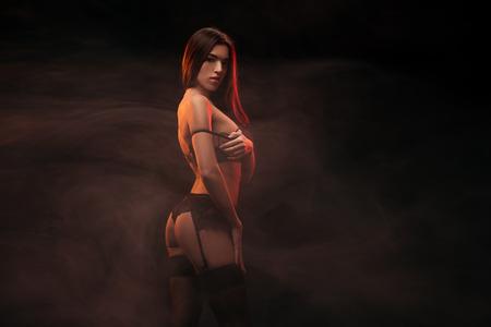 beautiful sensual woman in lingerie posing in dark smoky room