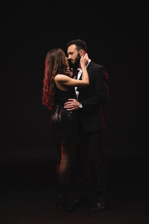 couple hugging and kissing isolated on black