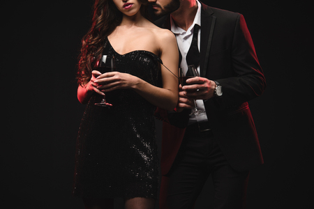 cropped view of seductive couple holding glasses with red wine isolated on black 免版税图像