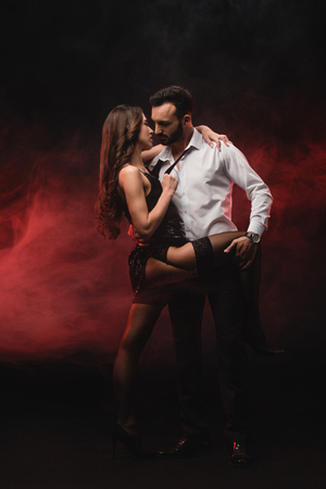 passionate loving couple hugging in red smoky room