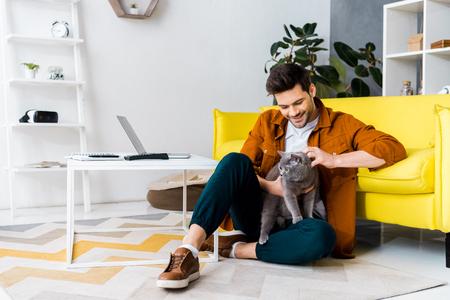 handsome smiling man sitting on floor with british shorthair cat Standard-Bild - 118650246