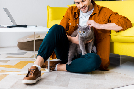 casual smiling man sitting on floor with british shorthair cat Standard-Bild - 118650247