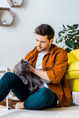casual smiling man sitting on floor with cute cat Standard-Bild - 118650249