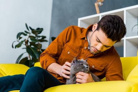 handsome man petting cute cat on sofa in living room Standard-Bild - 118650388