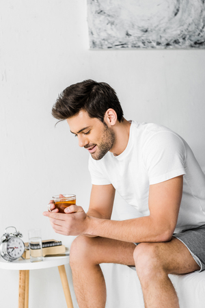 happy handsome man in pajamas holding cup of tea in bedroom Stock Photo