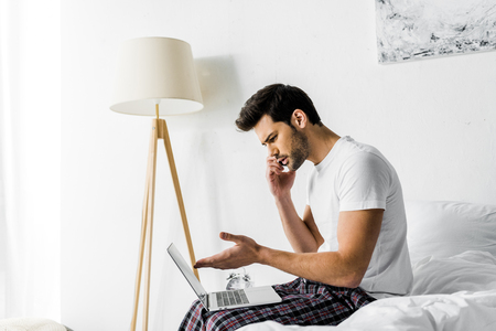 worried man talking on smartphone and using laptop on bed