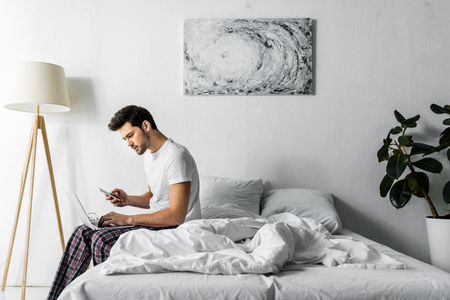 young man in pajamas using smartphone and laptop in bedroom