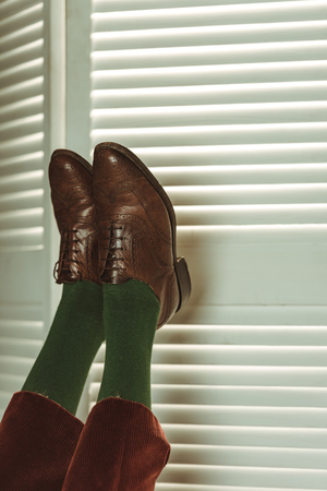 partial view of female legs in retro leather shoes near folding screen Stock Photo