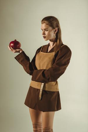 beautiful stylish model holding fresh pomegranate isolated on beige Stock Photo