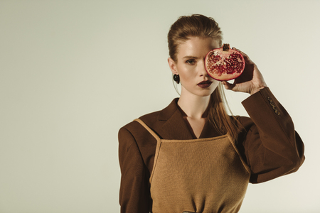 beautiful young woman holding half of pomegranate in front of the face isolated on beige 写真素材