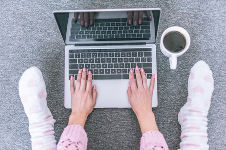 top view of female blogger typing on laptop keyboard near cup of coffee Stock Photo - 118655002
