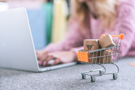 selective focus of small cart with toy paper boxes with woman using laptop on background Stock fotó - 118655163