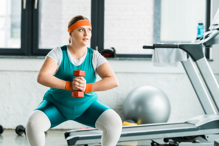 attractive overweight girl squatting with dumbbell in gym