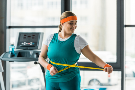 cheerful plus size girl looking at measuring tape while measuring waist in gym