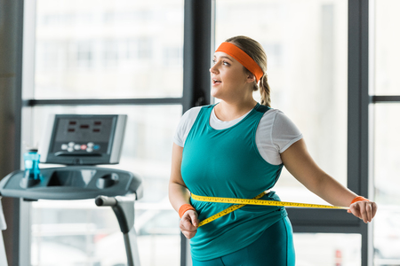 cheerful plus size girl measuring waist in gym Stok Fotoğraf