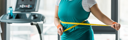 cropped view of plus size girl measuring waist in gym