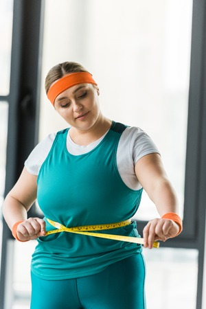 plus size girl looking at measuring tape while measuring waist in gym